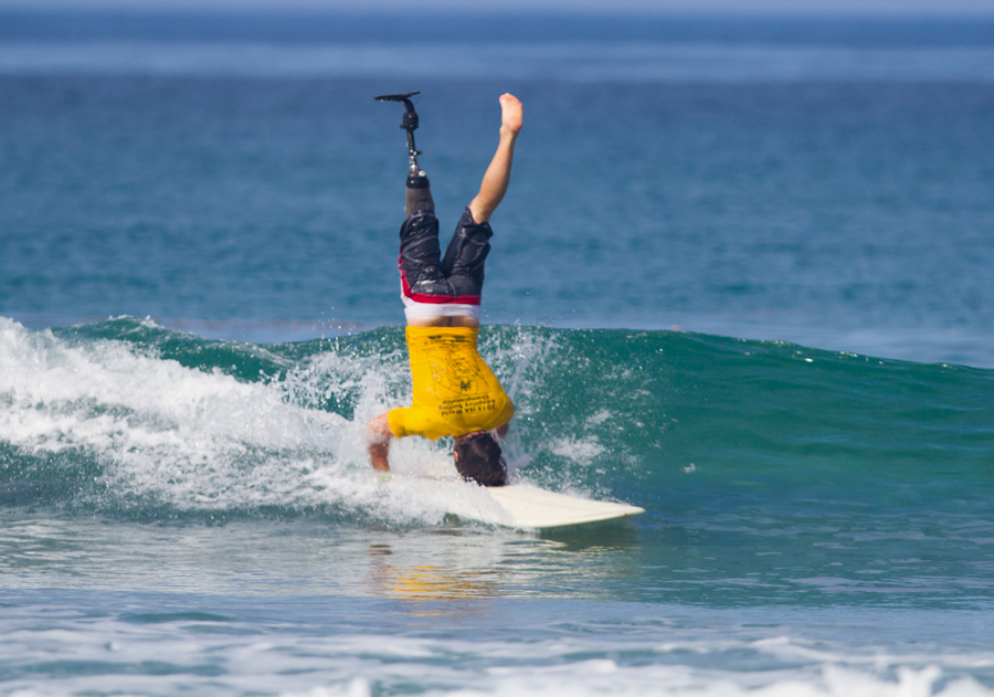 Ismael Guilliout doing a headstand on surfboard while surfing a wave