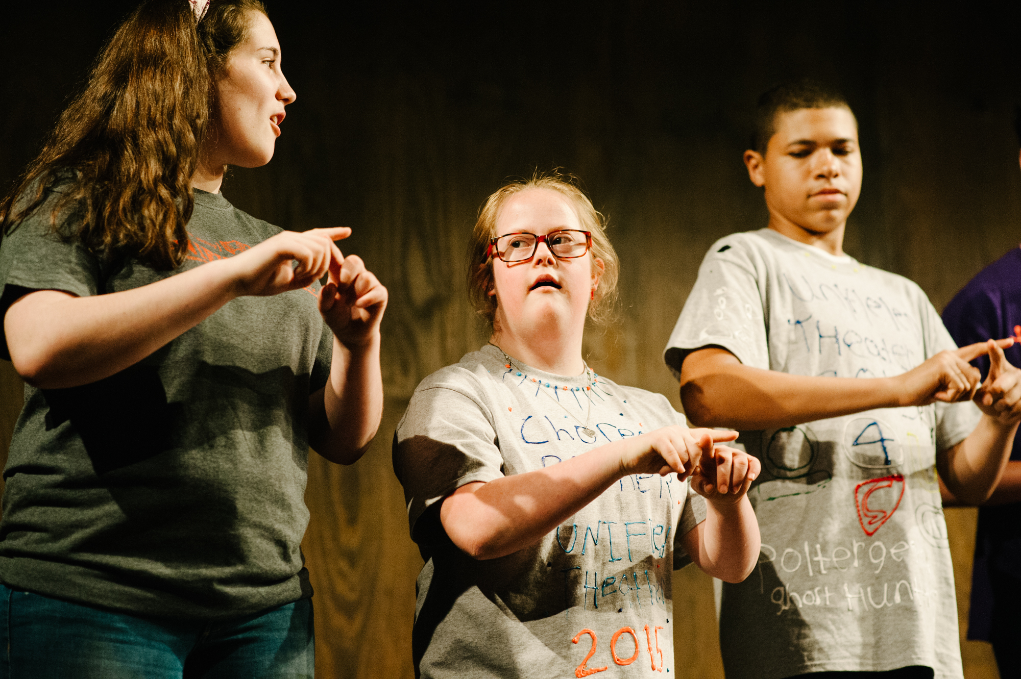 Three teens on stage performing the same sign language routine