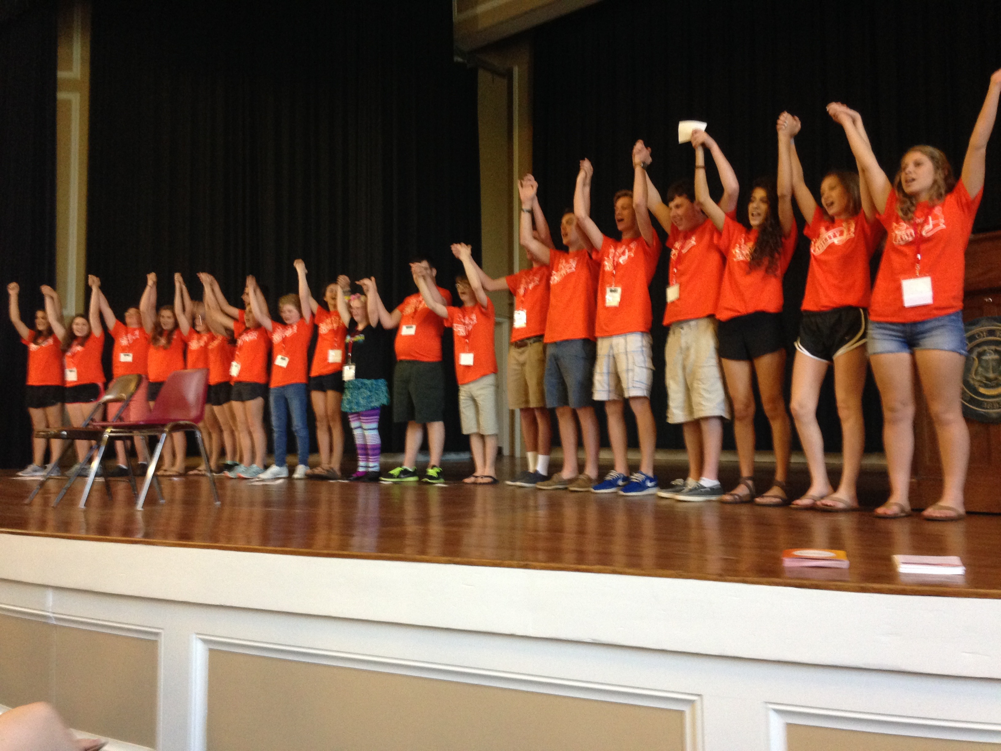 A line of teens on stage in a line, all wearing orange Unified Theater t-shirts