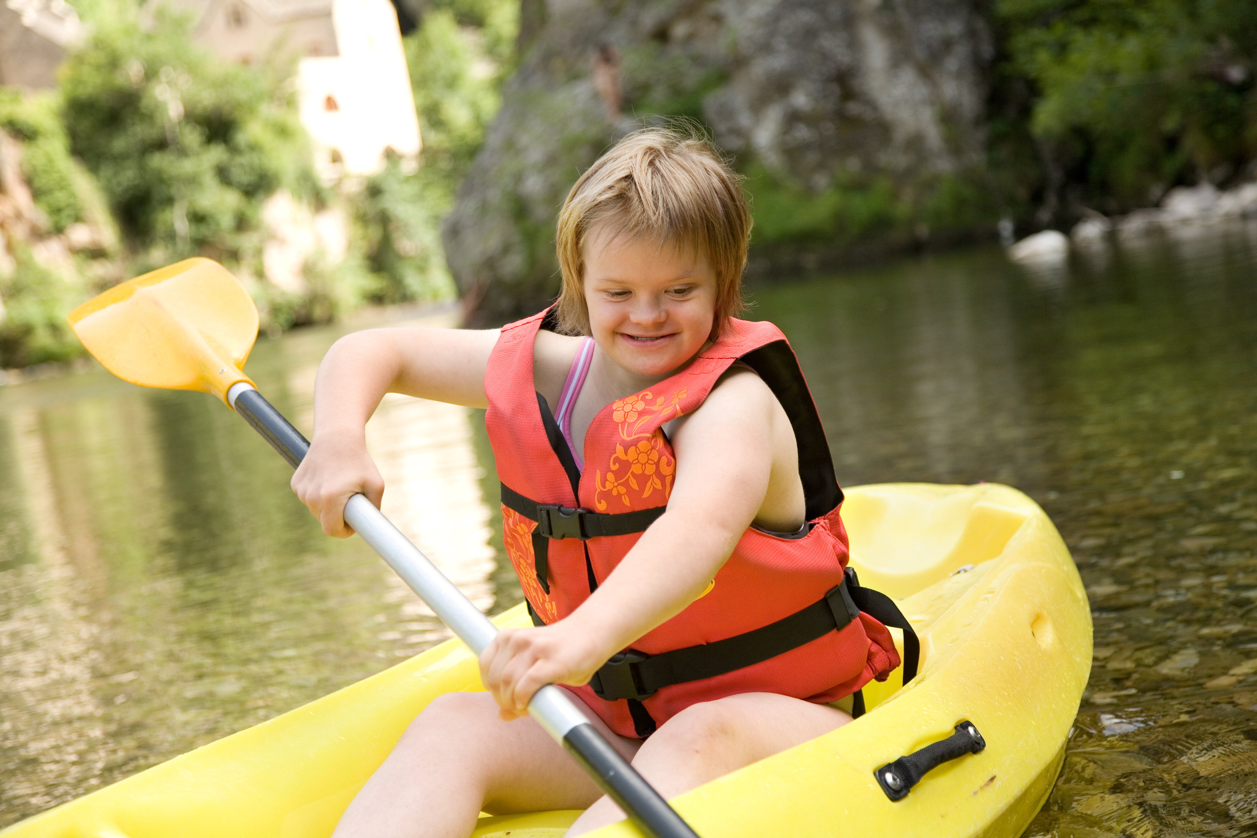 A teenaged girl with Down Syndrome kayaks while wearing a life vest
