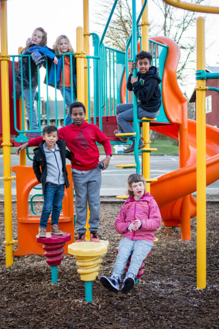 Children of various ages, races and abilities pose together on a playground.