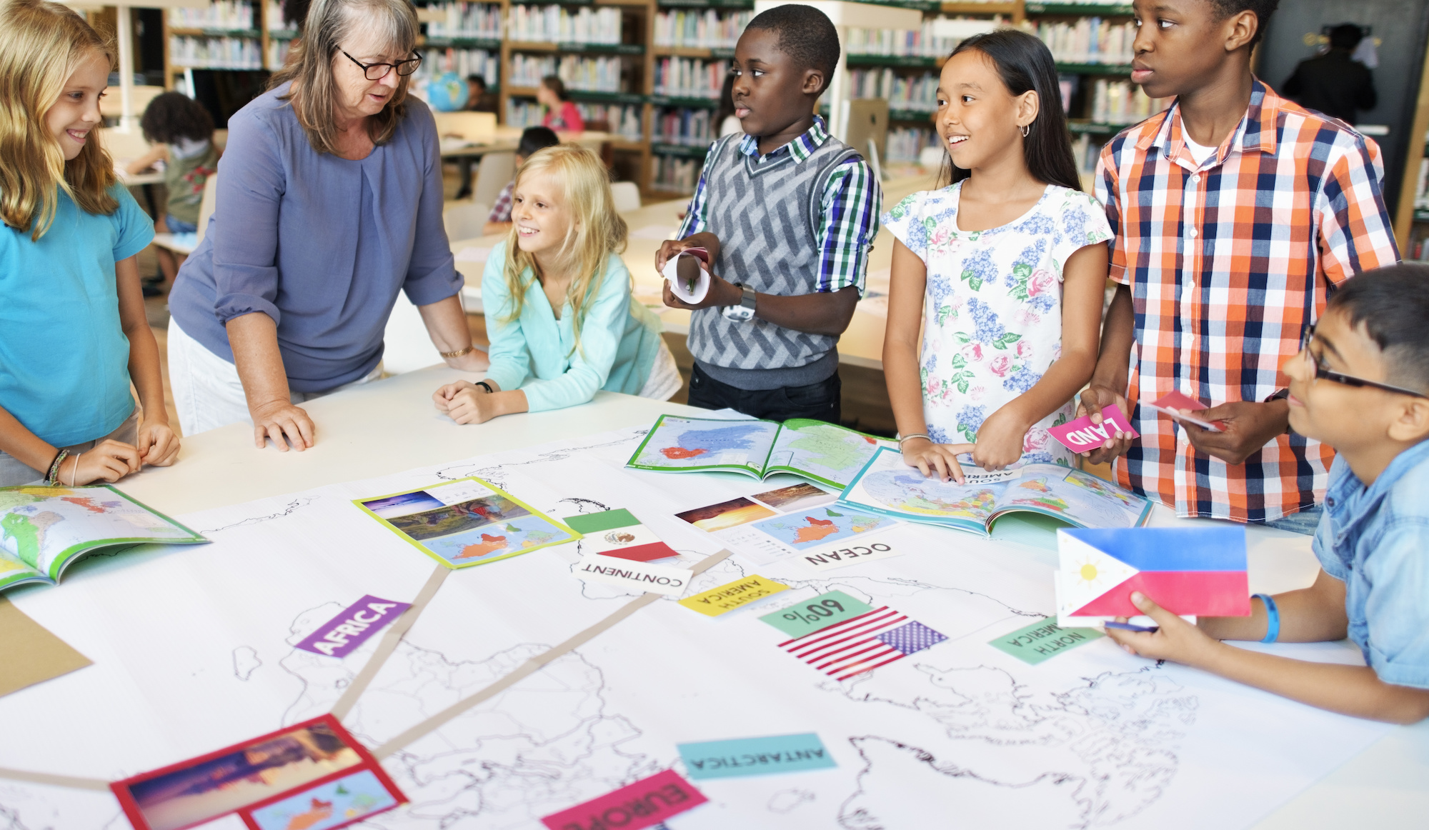 A group of middle school students are gathered around a table with a teacher looking at books and reports