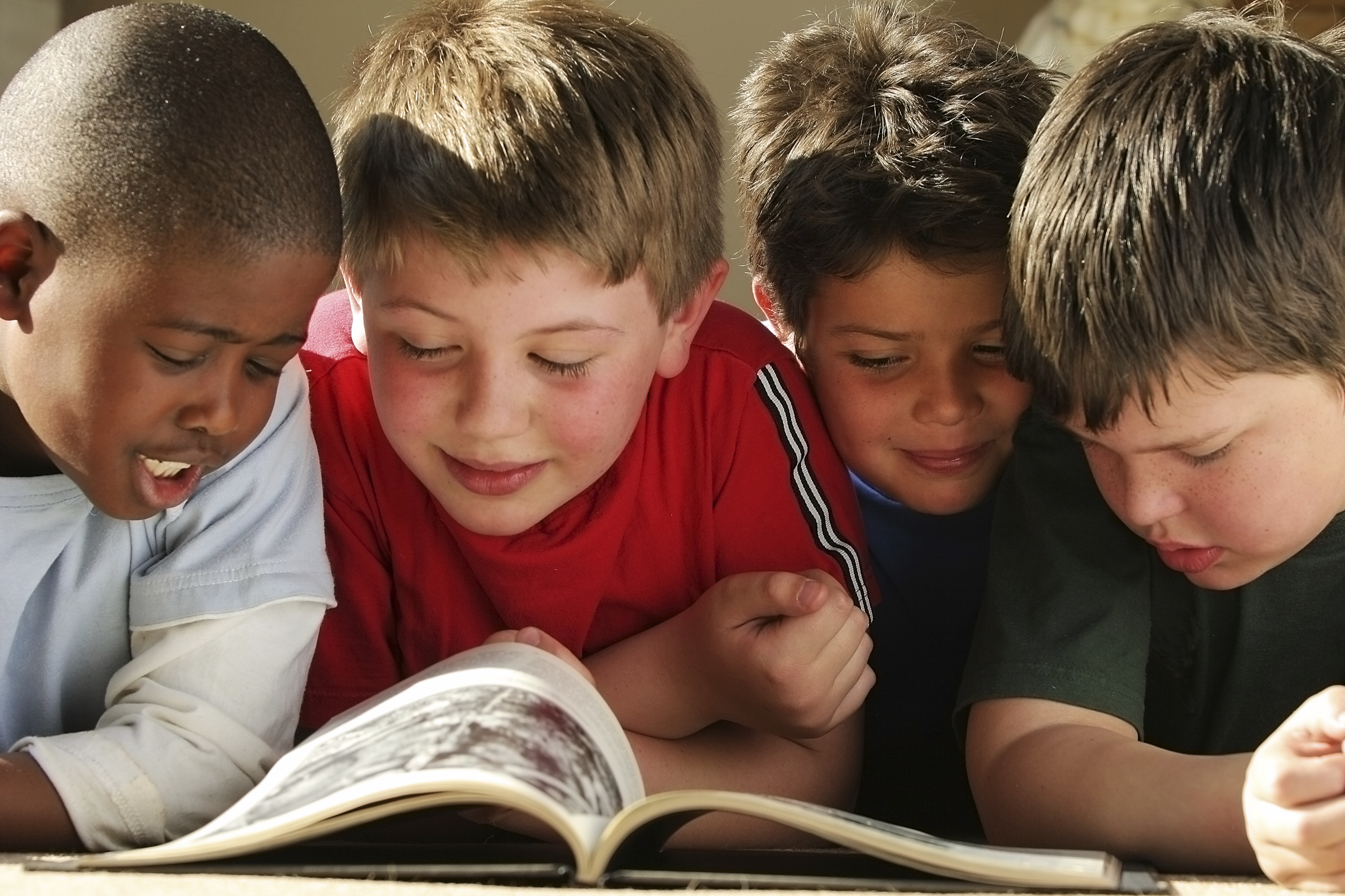 Close up photo of 4 boys leaning over a table reading a magazine