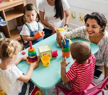 Provider interacting with preschool children in classroom