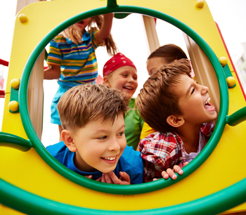 Kids smiling and playing on the playground