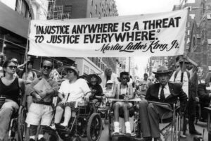"Photo of diverse people peacefully protesting and holding a sign with a quote from Martin Luther King, Jr saying ""Injustice Anywhere Is A Threat To Justice Everywhere."""