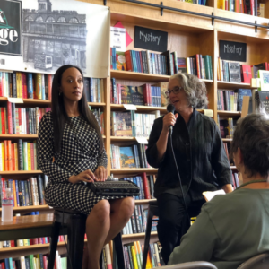 Haben Girma, a black woman, sitting on a tall stool in front of bookshelves with her communication device on her lap. A white woman sits next to her holding a microphone to her mouth, asking Haben a question.