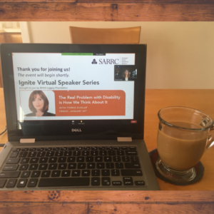 Image of a laptop computer screen with the introduction slide for the Ignite Virtual Speaker Series. Next to the laptop is a glass coffee mug with coffee in it.